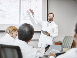 naukowcy w czasie dyskusji, prowadzący stoi przed ekranem