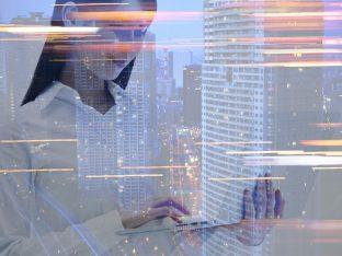 kobieta pracująca na laptopie, w tle drapacz chmur