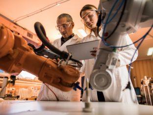 widok naukowców współpracujących przy pracy nad robotycznym ramieniem w laboratorium.
