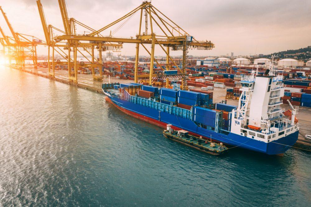 Widok z góry na port handlowy z żurawiem brzegowym ładującym kontenery na statek towarowy.