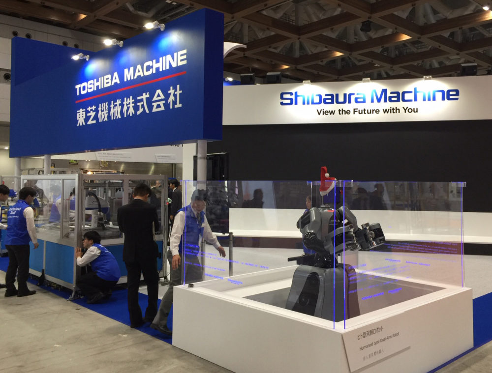 Stoisko na targach z robotem humanoidalnym Shibaura (Toshiba) Machine w czapce św. Mikołaja.