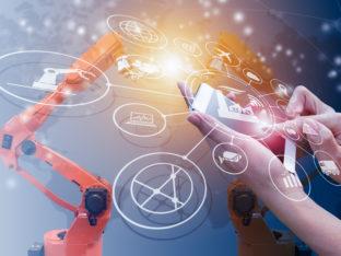 telefon trzymany w dłoniach, w tle robot przemysłowy