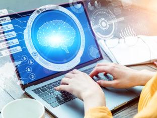 grafika; na monitorze wyświetla się mózg symbolizujący sztuczną inteligencję