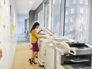 kobieta stojąca przy drukarce