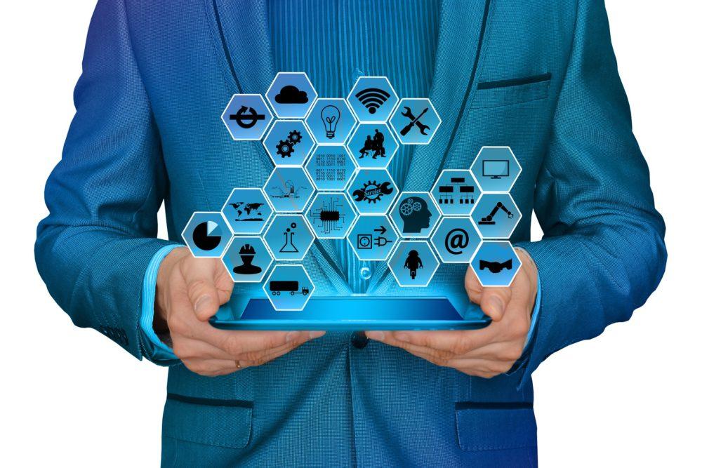 człowiek trzymający tablet, powyżej ekranu hologramy ikon prezentujących różne technologie