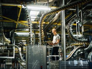 inżynier z komputerem przenośnym w fabryce