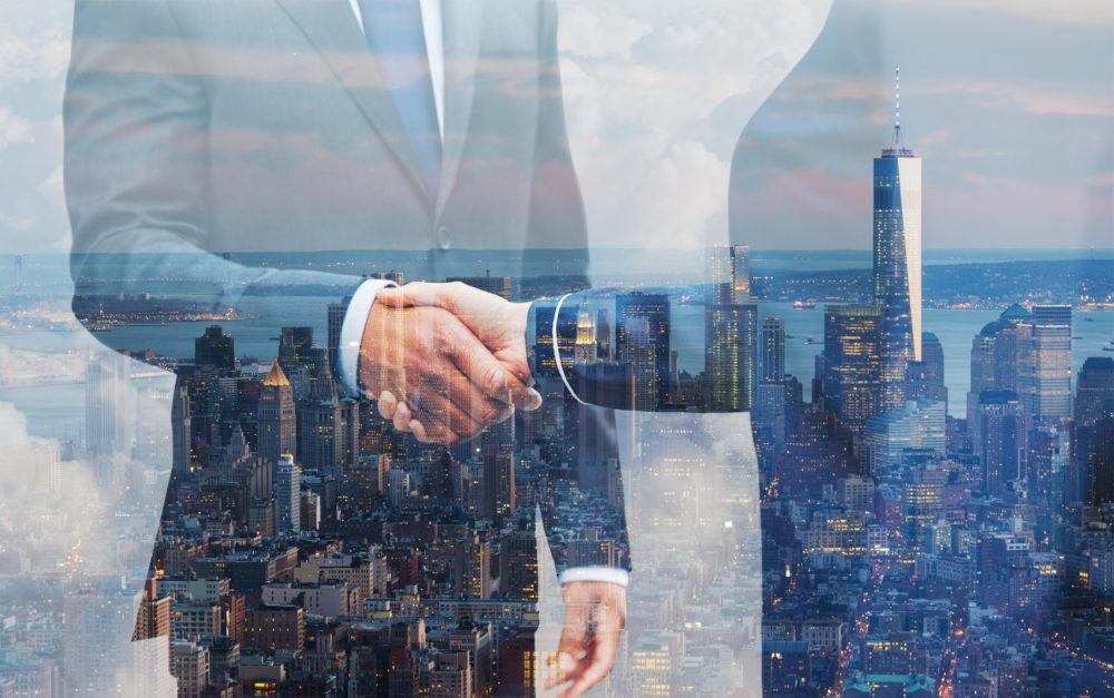 dwie osoby podające sobie dłoń, w tle Manhattan