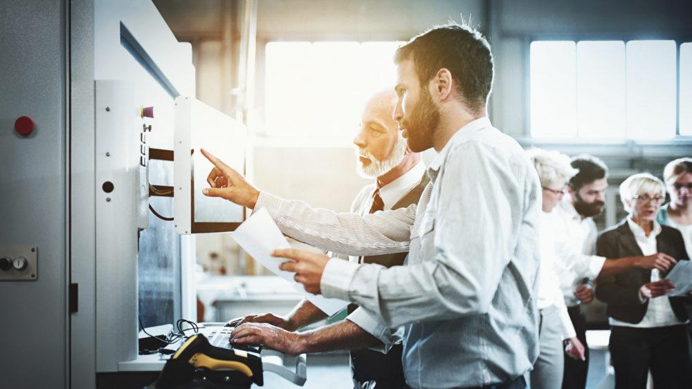 mężczyźni stojący przy maszynie CNC