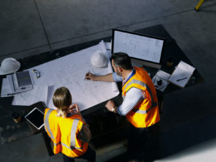 High angle shot of two engineers going over a blueprint together in an industrial place of work