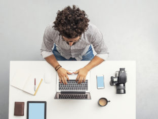 Man working at home office with laptop, camera, notepad and coffee on his desk, High angle view