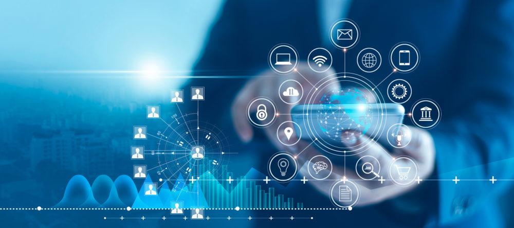 mężczyzna trzymający telefon, wokół grafiki prezentujące różne technologie