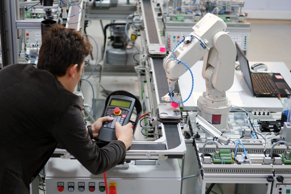 Man is working to control a robotic arm which is integrated on smart factory production line. industry 4.0 automation line which is equipped with sensors and robotic arm. Selective Focus.