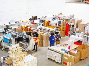 Ludzie pracujący na linii produkcyjnej w fabryce. Robotnicy pracujący przy maszynach i brygadzista kontrolujący produkty.