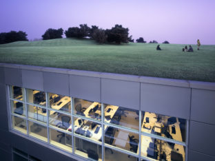 People taking a break in park landscape on top of modern office complex (composite image).