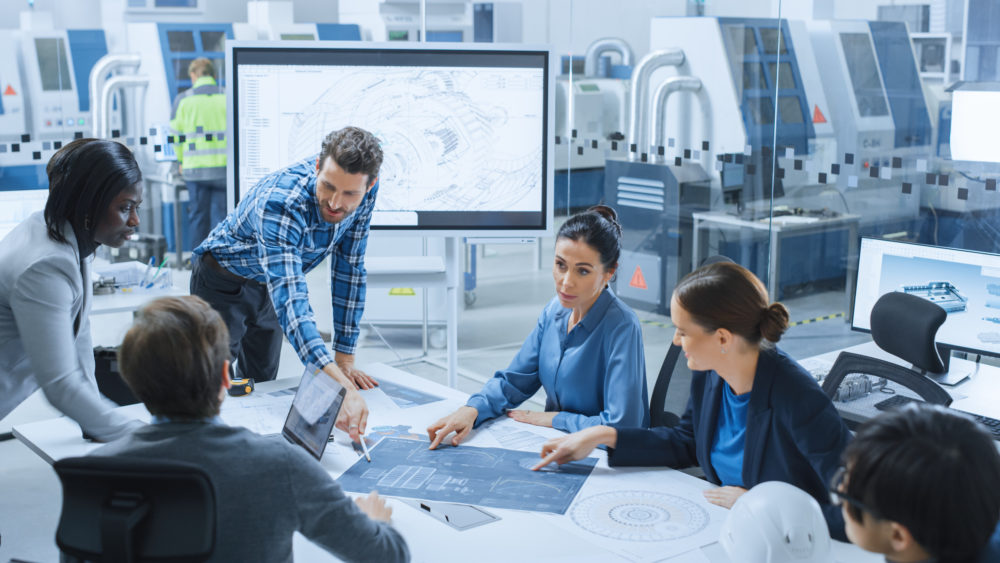 Modern Factory Office Meeting Room: Busy Diverse Team of Engineers, Managers and Investors Talking at Conference Table, Use Interactive TV, Analyze, Find Solutions, Debate and Discuss Engine Concept