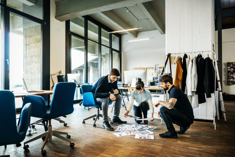 Creative new business people brainstorming on the floor of their modern office loft for ideas